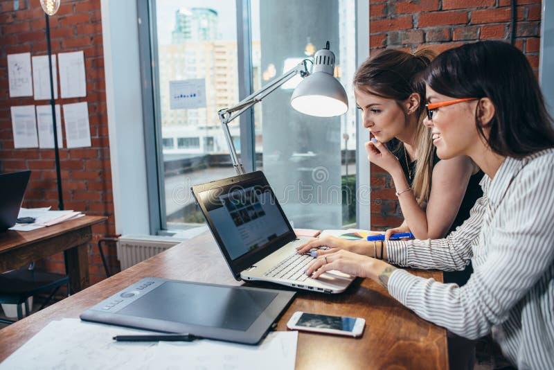 Duas mulheres que trabalham no Web site novo projetam a escolha de imagens usando o portátil que surfa o Internet imagem de stock royalty free