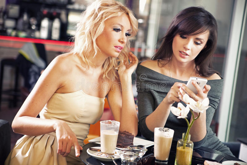 Duas mulheres que usam um smartphone foto de stock royalty free