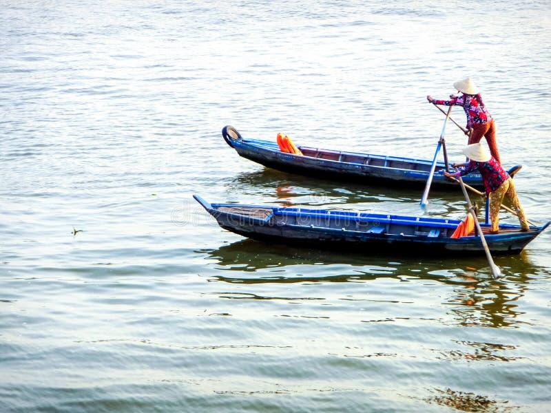 Duas mulheres que vestem o rowin vietnamiano tradicional colorido da roupa fotografia de stock