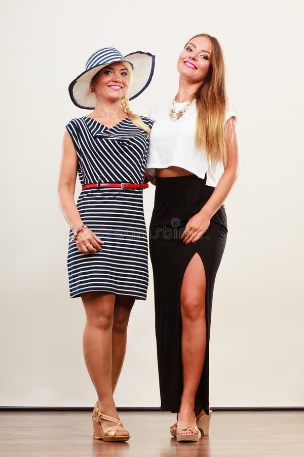 Duas mulheres que vestem vestidos elegantes fotografia de stock royalty free