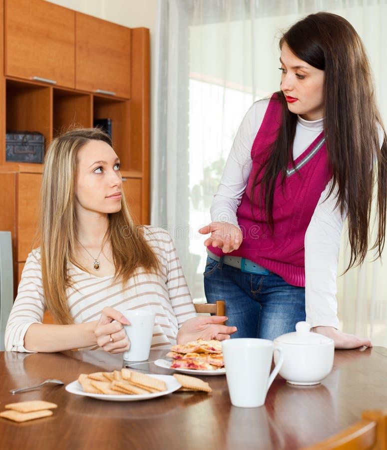 Duas mulheres sérias sobre a tabela de chá imagens de stock royalty free