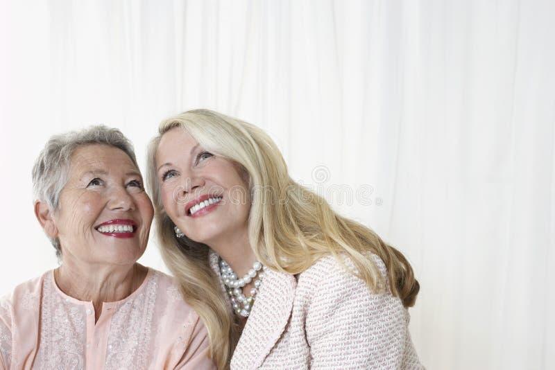 Duas mulheres superiores felizes que olham acima imagem de stock royalty free