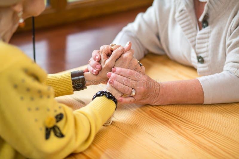 Duas mulheres superiores que guardam as mãos fotos de stock