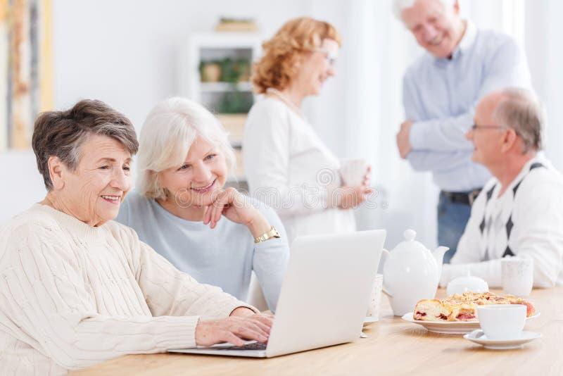 Duas mulheres superiores que usam o portátil foto de stock royalty free