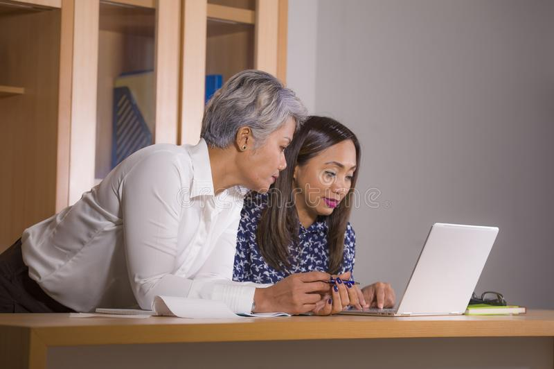 Duas mulheres trabalham os colegas ou os sócios comerciais que trabalham junto a leitura no laptop na cooperação e na colaboração fotografia de stock royalty free