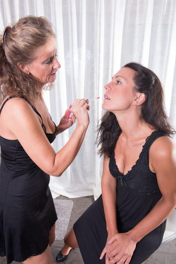 Duas mulheres, uma estão pondo a outro compõem sobre imagens de stock
