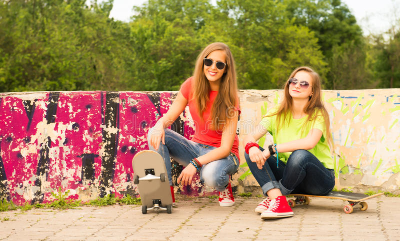 Duas namoradas adolescentes que têm o divertimento junto com a placa do patim Outd fotografia de stock royalty free