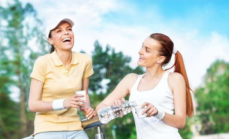 Duas namoradas de sorriso na água potável da roupa dos esportes fotografia de stock