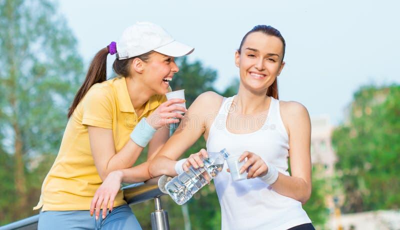 Duas namoradas de sorriso na água potável da roupa dos esportes foto de stock