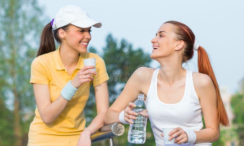 Duas namoradas de sorriso na roupa dos esportes imagem de stock royalty free