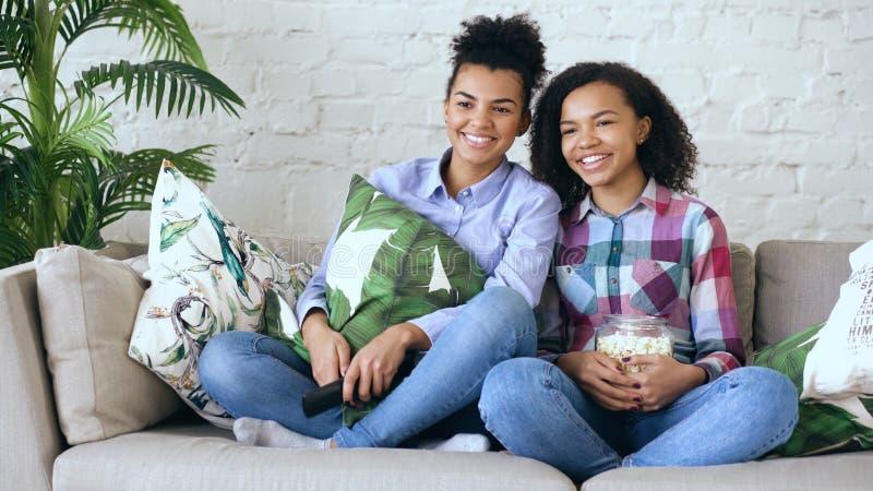 Duas namoradas encaracolado da raça misturada que sentam-se no filme da comédia do sofá e do relógio e comem a pipoca Irmãs engra imagens de stock royalty free