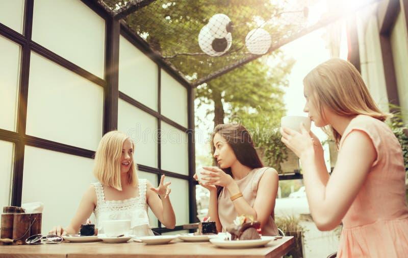 Duas namoradas passam o tempo que bebem junto o café no café, comendo o café da manhã e a sobremesa fotografia de stock royalty free