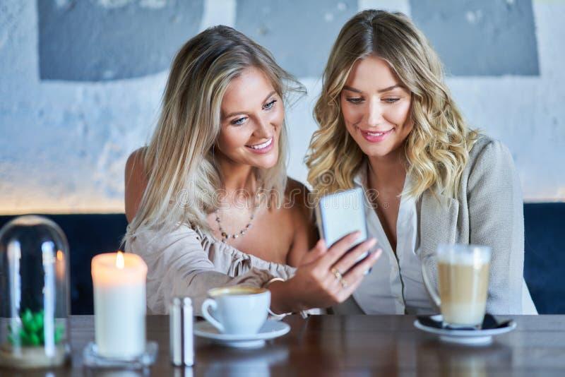 Duas namoradas que comem o almoço no restaurante e que usam o smartphone imagens de stock