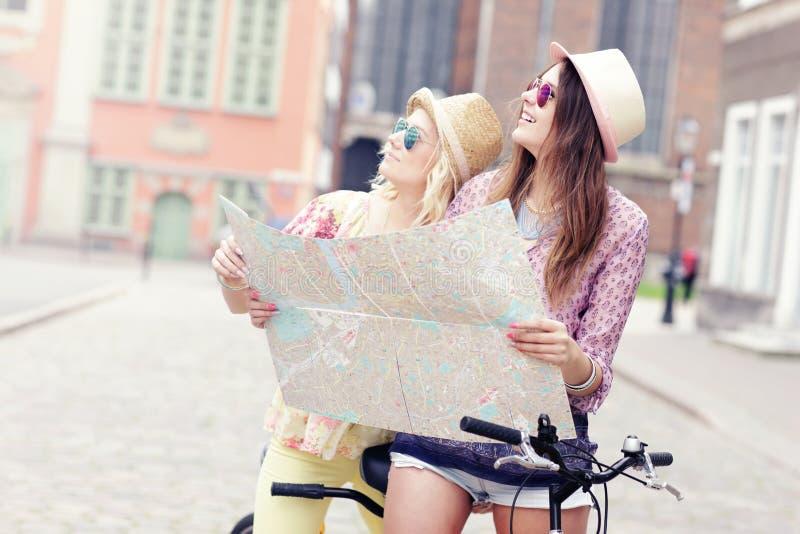 Duas namoradas que usam o mapa ao montar a bicicleta em tandem fotografia de stock royalty free