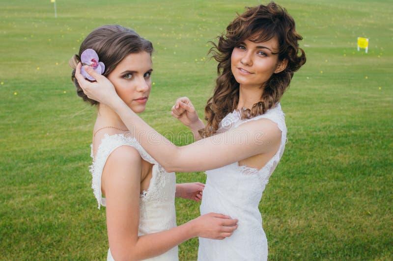 Duas noivas bonitas que corrigem o cabelo no campo verde fotos de stock