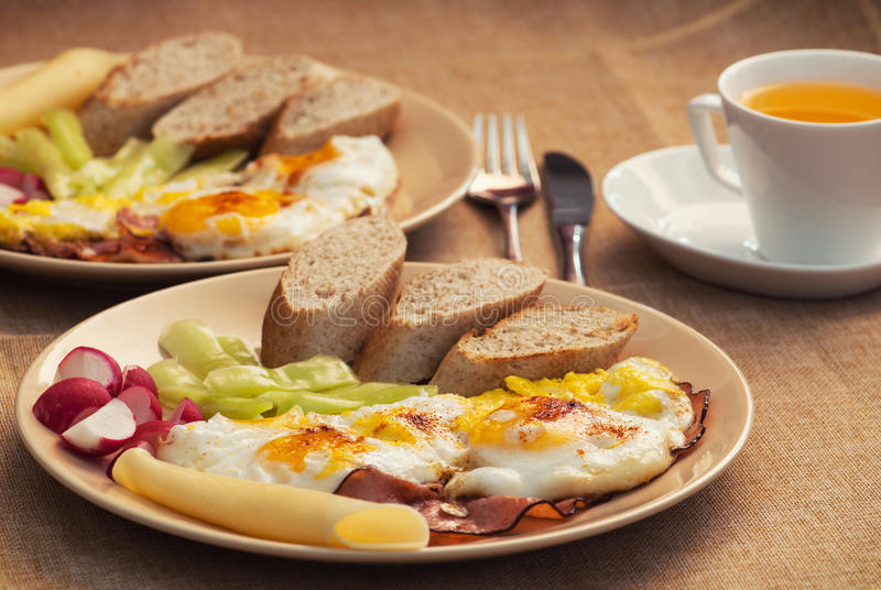 Duas parcelas de presunto e de ovos com pão, rabanete, queijo e papr fotos de stock royalty free