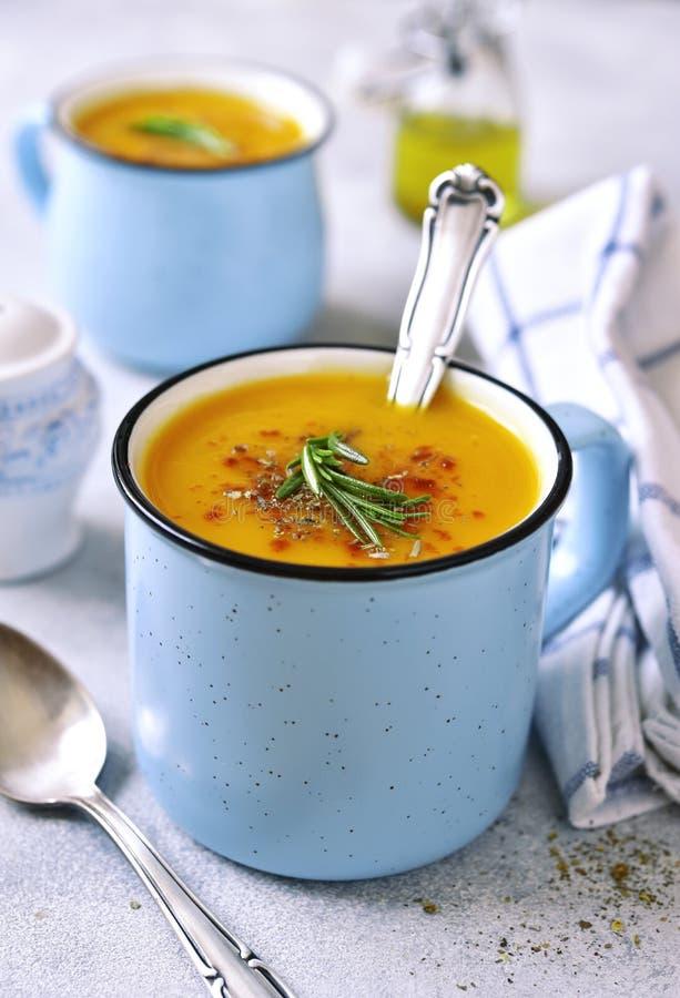 Duas parcelas de sopa cremosa da abóbora em um emamel do azul agridem fotografia de stock