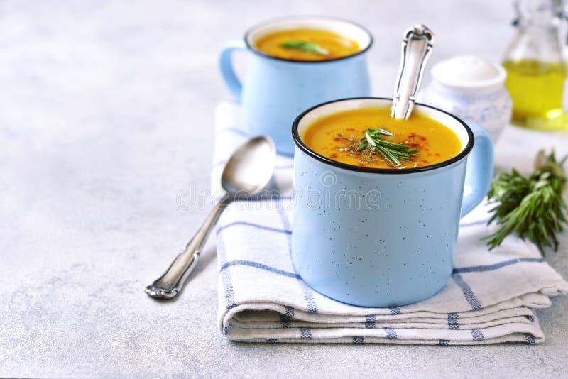 Duas parcelas de sopa cremosa da abóbora em um emamel do azul agridem fotos de stock