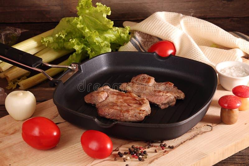 Duas partes de bifes grelhados da carne de porco sobre ao fritar a bandeja da grade fotos de stock