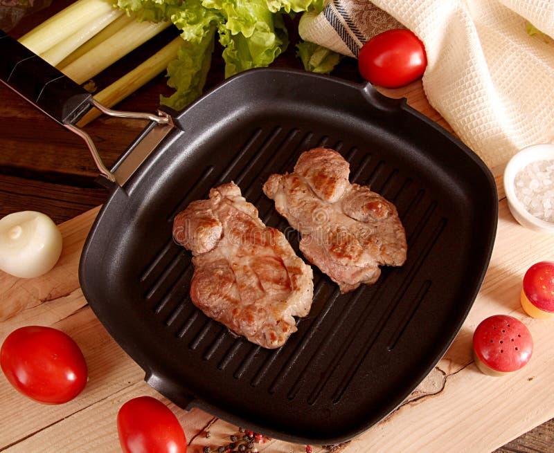 Duas partes de bifes grelhados da carne de porco sobre ao fritar a bandeja da grade fotos de stock royalty free