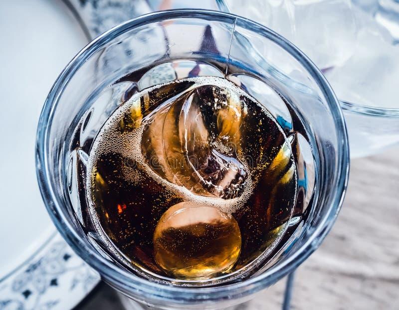 Duas partes de flutuador do gelo em um vidro com uma bebida carbonatada escura fotografia de stock