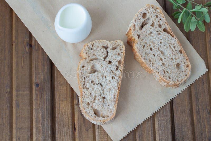 Duas partes de pão e de copo do leite fotografia de stock