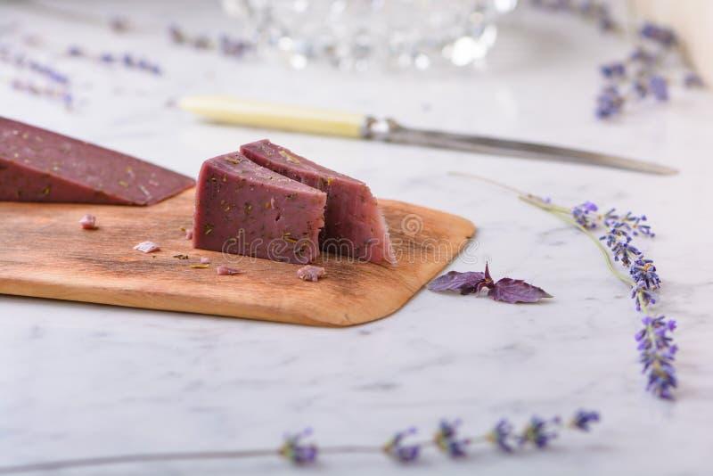 Duas partes de queijo da alfazema e de flores da alfazema na placa de corte de madeira no worktop de mármore branco foto de stock
