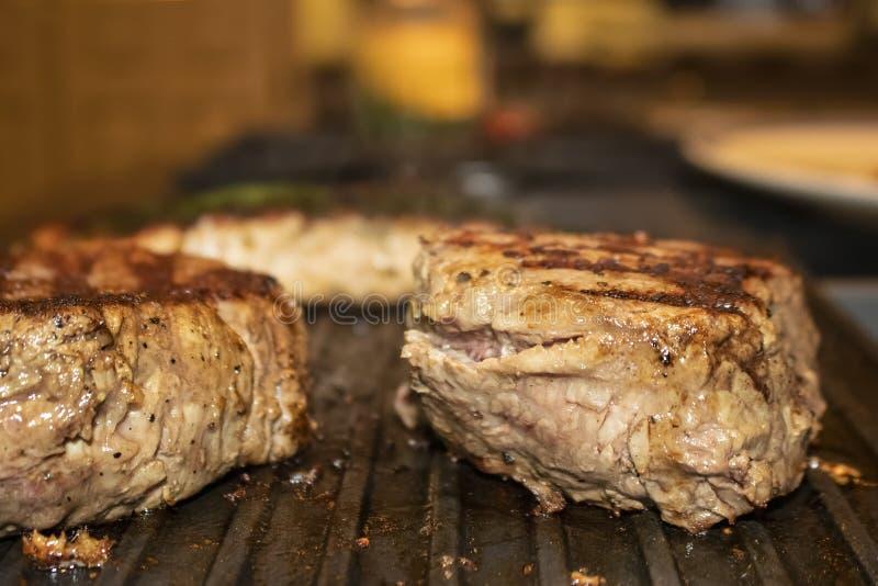 Duas partes parcialmente cozinhadas suculentas de faixa da carne com exibição cor-de-rosa dentro do cozimento em uma grade do sto foto de stock