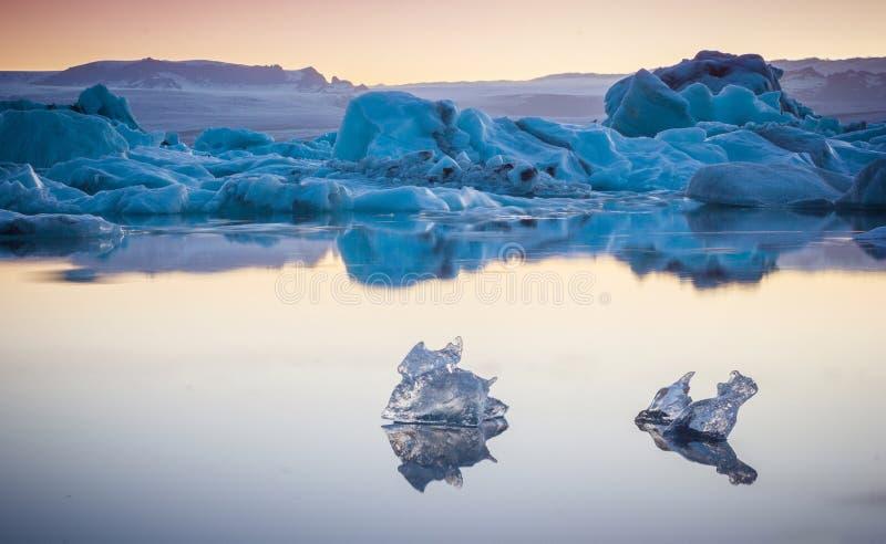 Duas partes pequenas de gelo que fluem e que refletem no lago frio com iceberg grandes atrás, lagoa da geleira do jokulsarlon, Is foto de stock royalty free