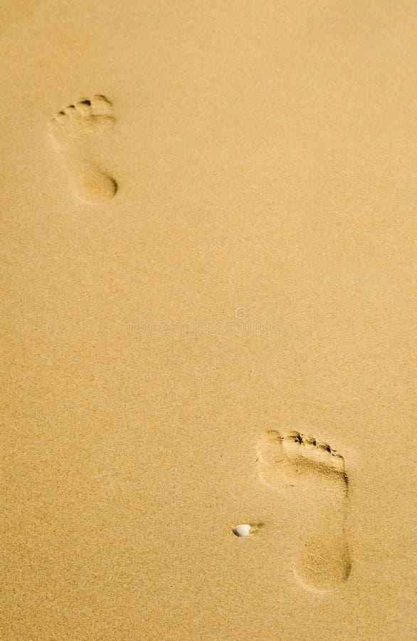 Duas pegadas na areia desobstruída do ouro imagens de stock royalty free