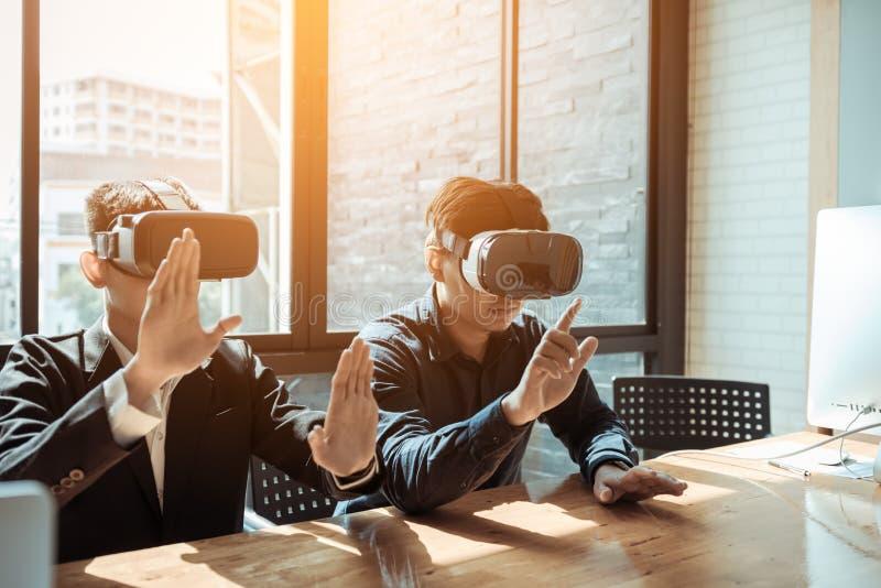 Duas pessoas do negócio do negócio com os auriculares da realidade virtual em t foto de stock