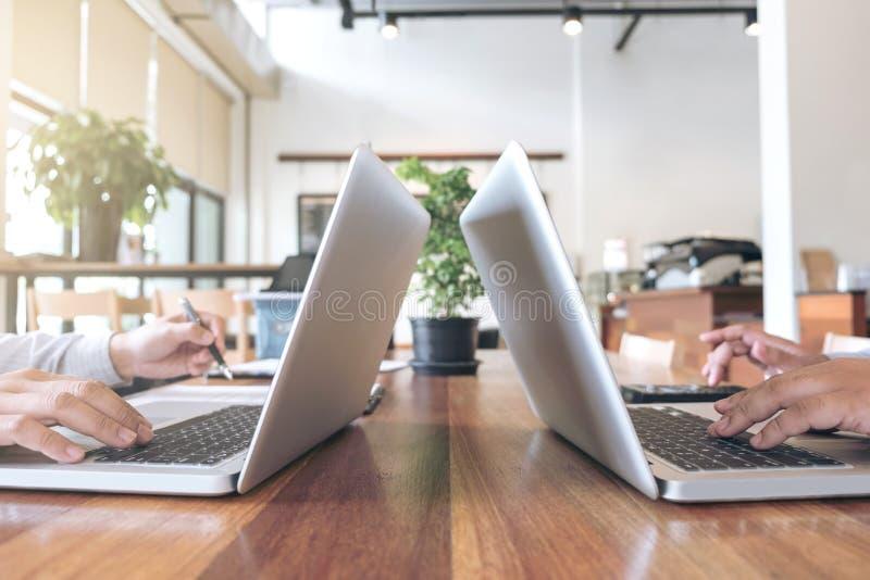 Duas pessoas do negócio que trabalham na mesa de escritório e que discutem usando-se fotografia de stock royalty free