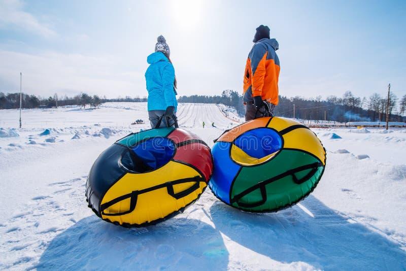 Duas pessoas puxam trenós para a parte superior do monte Tubulação da neve imagem de stock royalty free