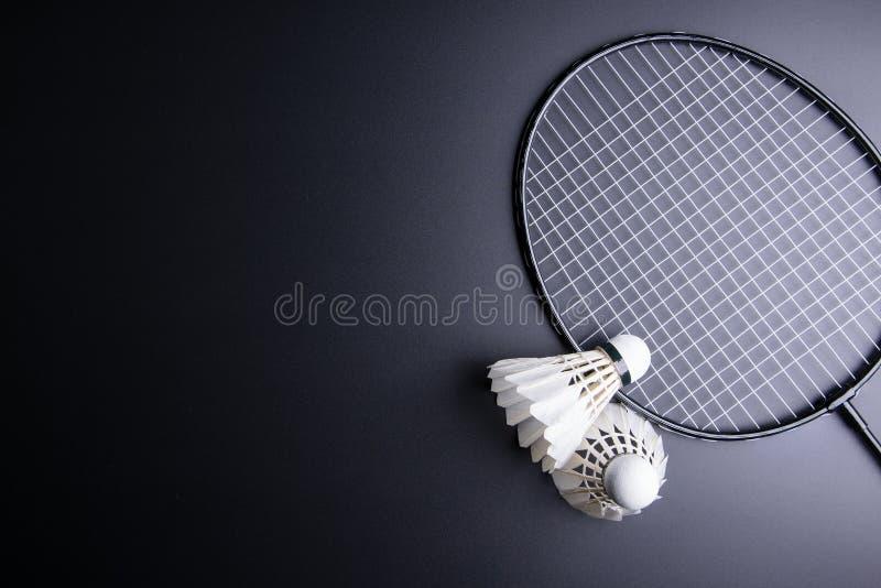 Duas petecas e raquetes de badminton no fundo preto esporte imagens de stock royalty free