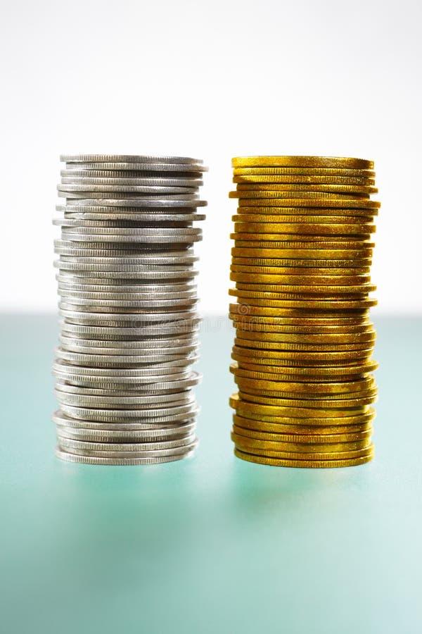 Duas pilhas de moedas da prata e de ouro imagens de stock royalty free
