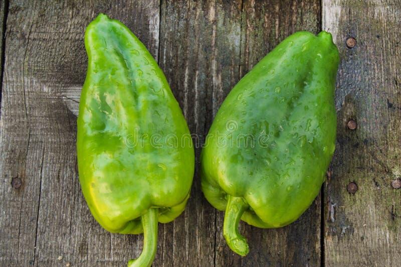 Duas pimentas de sino cruas verdes em uma placa de madeira escura velha, em gotas da água em legumes frescos orgânicos, em dieta  imagem de stock royalty free