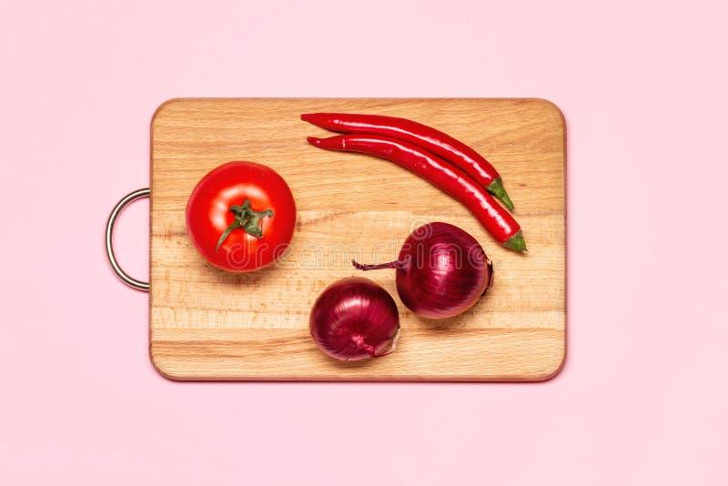 Duas pimentas frescas de Violet Bow Near Red Chilli e um tomate fotografia de stock royalty free