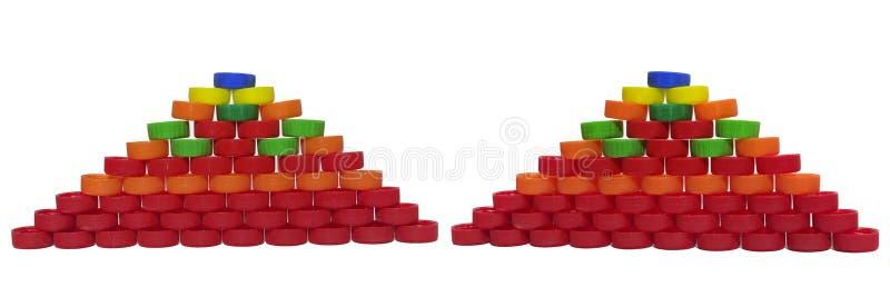 Duas pirâmides feitas fora dos tampões plásticos coloridos para o bottl da bebida foto de stock