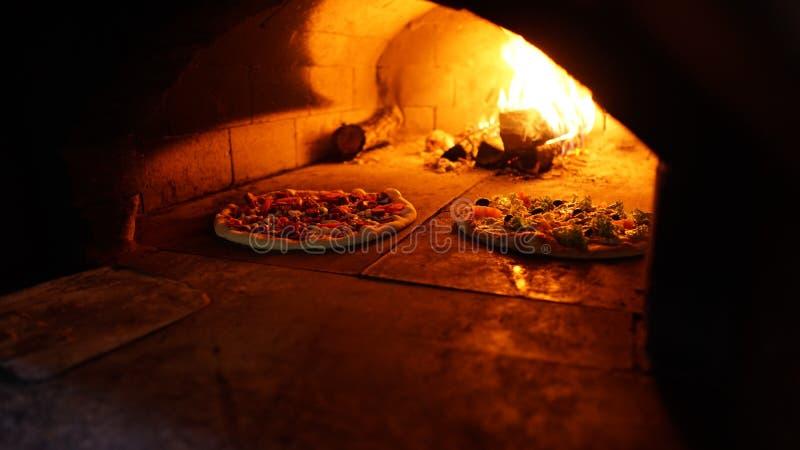 Duas pizzas no forno de pedra estão cozinhando imagem de stock