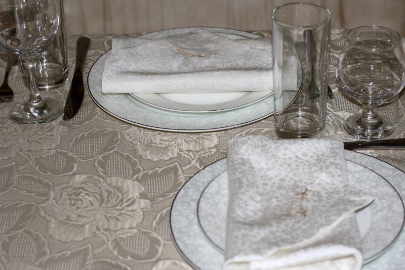 Duas placas brancas com guardanapo, vidros de vinho, forquilhas e facas em uma tabela coberta com uma toalha de mesa de seda Tabe imagens de stock royalty free