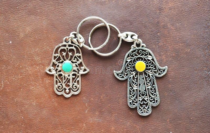 Duas portas-chaves sob a forma de Fatima Hand em um fundo de couro marrom Símbolo antigo e lembrança moderna tradicional do turis imagens de stock