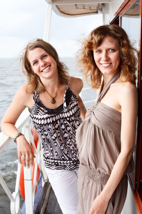 Duas raparigas bonitas na plataforma do navio foto de stock