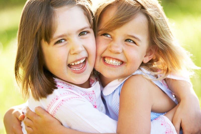 Duas raparigas que dão a uma outra o Hug foto de stock royalty free