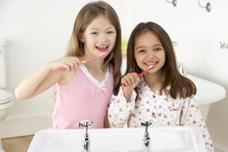 Duas raparigas que escovam os dentes no dissipador imagens de stock