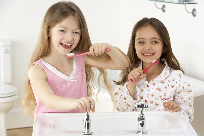 Duas raparigas que escovam os dentes no dissipador fotografia de stock royalty free