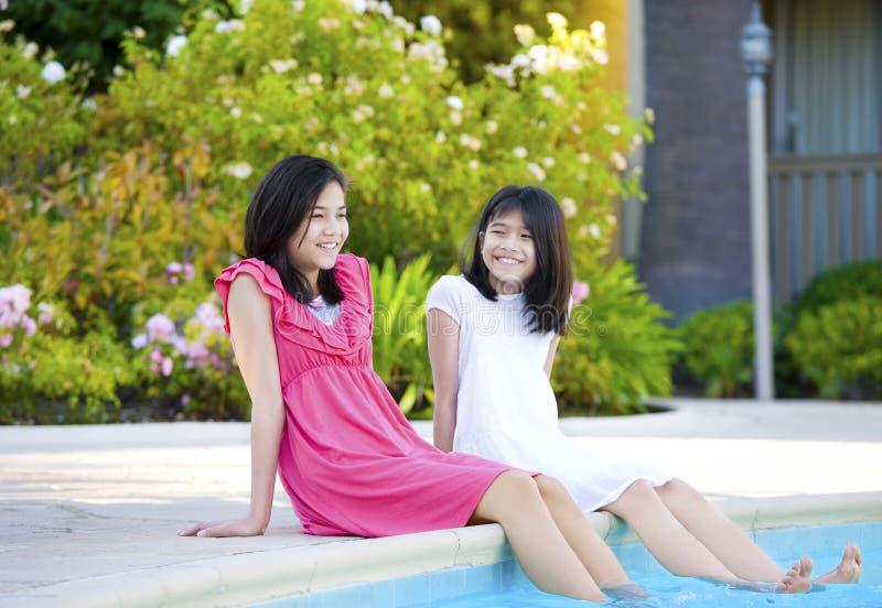 Duas raparigas que sentam-se pela piscina, sorrindo foto de stock royalty free
