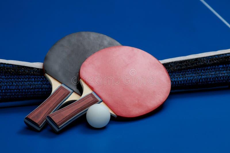 Duas raquetes do pong do sibilo Raquetes de tênis de mesa e uma bola em uma tabela azul do tênis fotos de stock
