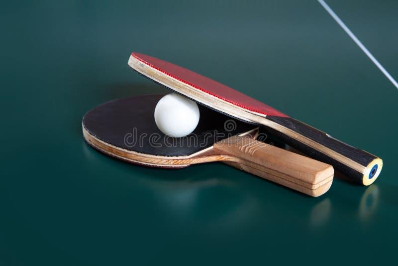 Duas raquetes do t?nis de mesa e uma bola em uma tabela azul Rede do t?nis de mesa imagem de stock