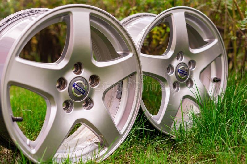 Duas rodas de alumínio originais velhas de Volvo Usado, fora, na grama verde imagem de stock royalty free