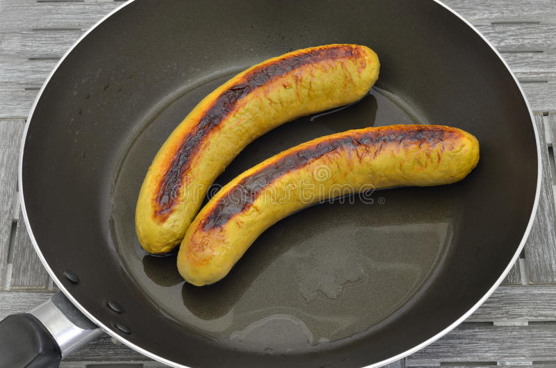 Duas salsichas grelhadas em uma frigideira imagem de stock royalty free